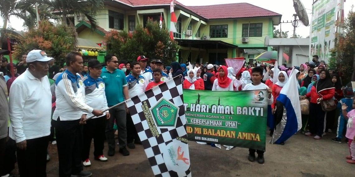 Sekdakot Banjarbaru Drs H Said Abdullah didampingi Ketua DPRD Kota Banjarbaru AR Iwansyah, menandai dimulainya jalan santai dengan mengibarkan bendera start. Foto - Dema