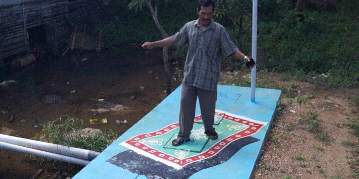 Ketua RT 04 RW 01 Kelurahan Kemuning, Najaruddin, saat berpose di atas septic tank yang ada lukisan karpet terbangnya. Foto - Dema