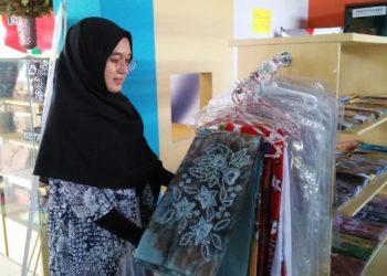 Salah seorang karyawati cantik yang bekerja di Rumah Kreatif Banjarbaru saat memperlihatkan produk sasirangan. Foto - Dema