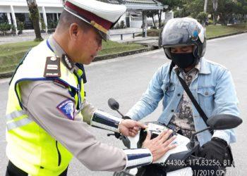 Polantas Polres Banjarbaru menempelkan stiker himbauan berlalu lintas. Foto - ist