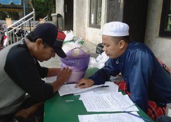 Petugas BAZ Masjid Jami' Hidayatul Muhajirin Banjarbaru bimbing pembayar zakat fitrah membaca niat. Foto - Rizky